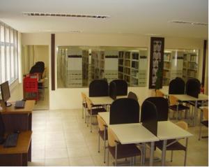 Imagem das mesas de estudo individual da biblioteca da Faculdade de Educação, com as estantes de livros ao fundo.