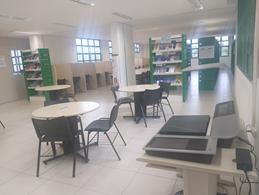 Imagem da biblioteca de Farmácia e Odontologia com o scanner planetário a direita, as mesas de estudo em grupo ao centro, as baias de estudo individual ao fundo e à esquerda e as estantes de livros ao fundo à direita.