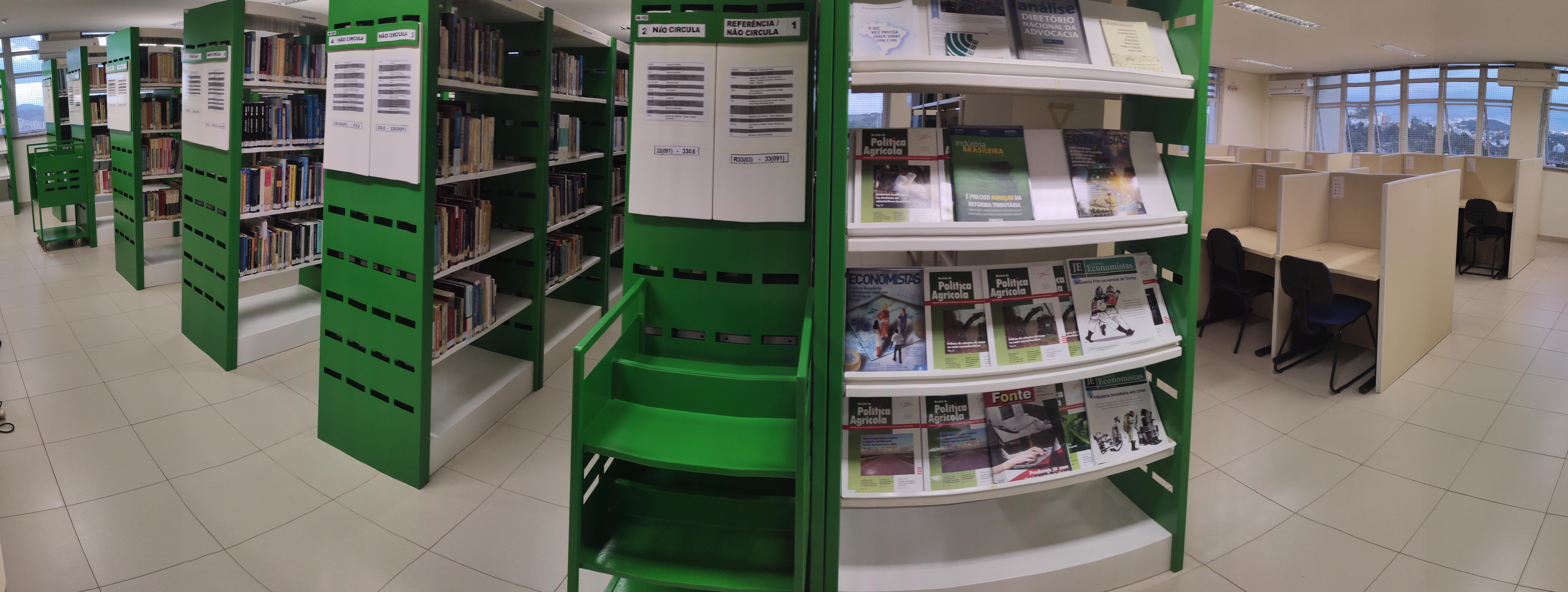 Imagem das estantes de livros e das mesas de estudo individual da biblioteca da economia.