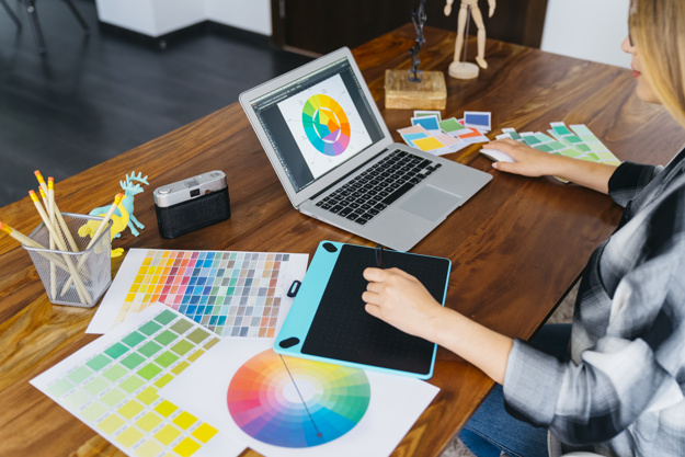 graphic-designer-with-laptop-and-graphic-tablet_23-2147652928