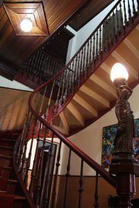 Foto da escada interna do Forum da Cultura, com luminária e bronze dourado