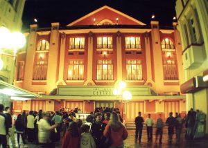 A imagem mostra grupos de pessoas conversando em frente à fachada do Cine-Theatro Central, iluminada através de seus vitrais e postes de luz. Ao fundo, há uma carrocinha de pipoca e pessoas em volta.