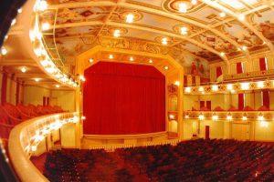 A foto apresenta a visão geral do Cine-Theatro Central, vista dos bancos à esquerda do palco. Abaixo estão os assentos de cor vinho da plateia do primeiro andar, do balcão nobre, do camarote e os da galeria.