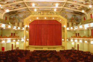 A foto mostra o palco do Cine-Theatro Central em evidência no centro com suas grandes cortinas vermelhas fechadas. Em torno da imagem aparecem parte dos assentos de cor vinho da plateia do térreo, os do segundo e terceiro andares do teatro, e parte do teto pintado por Ângelo Bigi com todas as luzes acesas.