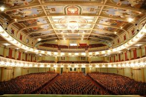 Cine-Theatro Central do ponto de vista do palco, exibindo seus três andares de assentos, pinturas, teto e luzes acesas.