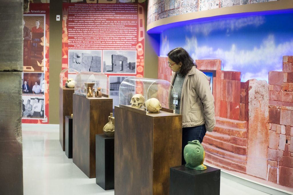 A foto mostra uma visitante observando parte da coleção antropológica do MAEA, na Sala Franz Hochleitner. Na imagem, temos alguns crânios e peças em argila exibidos em expositores. As paredes são ilustradas por imagens e textos didático-informativos sobre o Museu e seu acervo.
