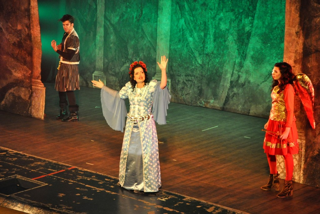 A foto mostra três pessoas encenando a Ópera de Monteverdi durante o Festival Internacional de Música Colonial Brasileira e Música Antiga. Ao lado direito do palco está uma mulher vestida de vermelho, enquanto observa outra mulher com um longo vestido azul contracenando no centro. No lado esquerdo da imagem um homem vestido em roupas marrons também observa.