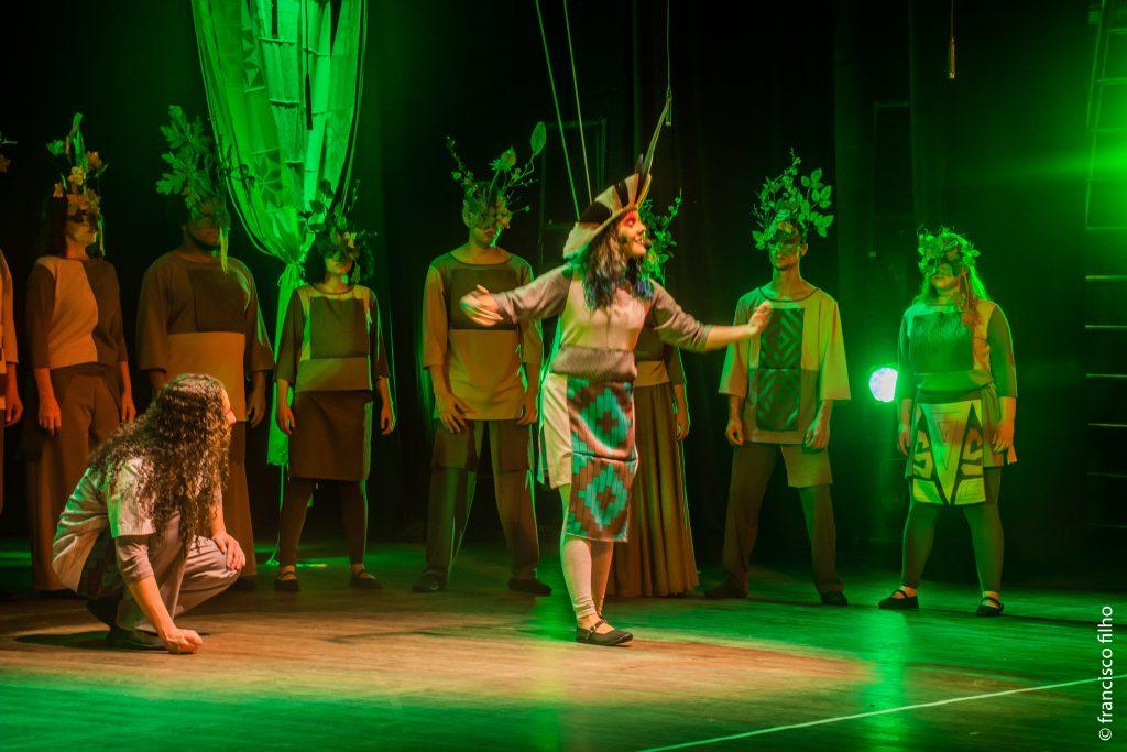 A imagem mostra 10 integrantes do Coral Universitário durante uma apresentação: uma mulher em pé está vestida com adereços típicos da cultura indígena; à esquerda um homem agachado a observa e, ao fundo do palco, outros integrantes estão de pé, utilizando máscaras de galhos e folhagens.