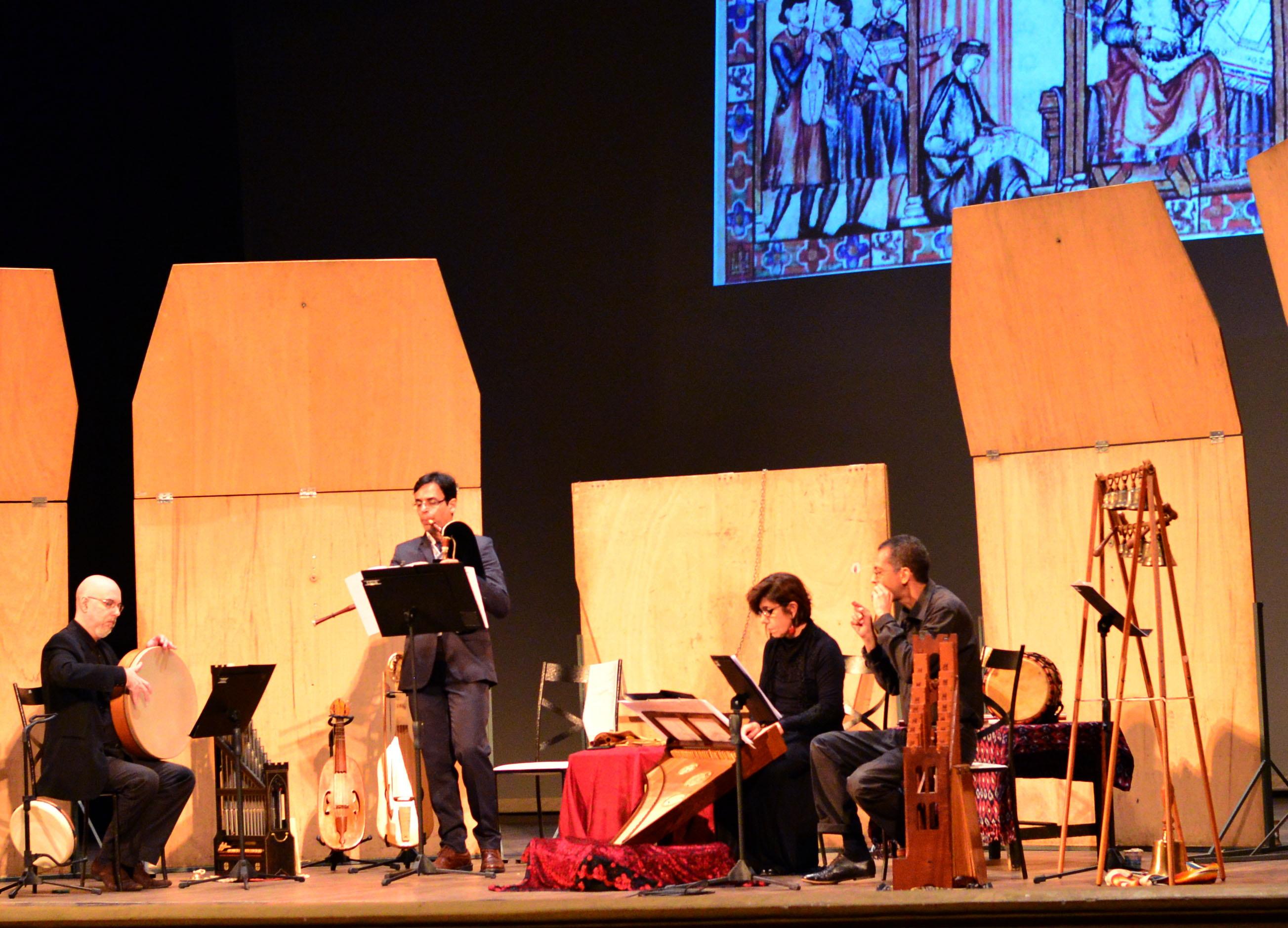 A imagem contém quatro músicos do Conjunto Atempo se apresentando no Festival Internacional de Música Colonial Brasileira e Música Antiga: um homem em pé está seguindo uma partitura enquanto toca seu instrumento musical junto a dois homens e uma mulher que estão sentados, também tocando. Ao fundo do palco está refletida uma imagem de uma pintura medieval que representa músicos trovadores.