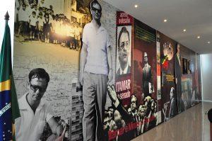A imagem mostra um painel que estampa um recorte da vida pública, política e econômica do presidente Itamar Franco. O painel conta com fotos coloridas, preto e branco e em sépia. Além disso, a bandeira do Brasil também está disposta ao lado painel.