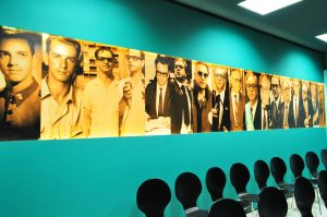 A foto apresenta a Sala de Vídeo do Memorial, com algumas cadeiras enfileiradas, além de fotos marcantes da trajetória de vida de Itamar Franco, que são exibidas na parede do espaço.