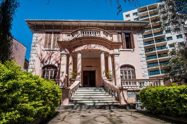 A imagem apresenta a fachada do Fórum da Cultura, construída por influência neoclássica e foi inspirada nas villas italianas. Em frente à construção, há diversas folhagens e árvores do jardim.