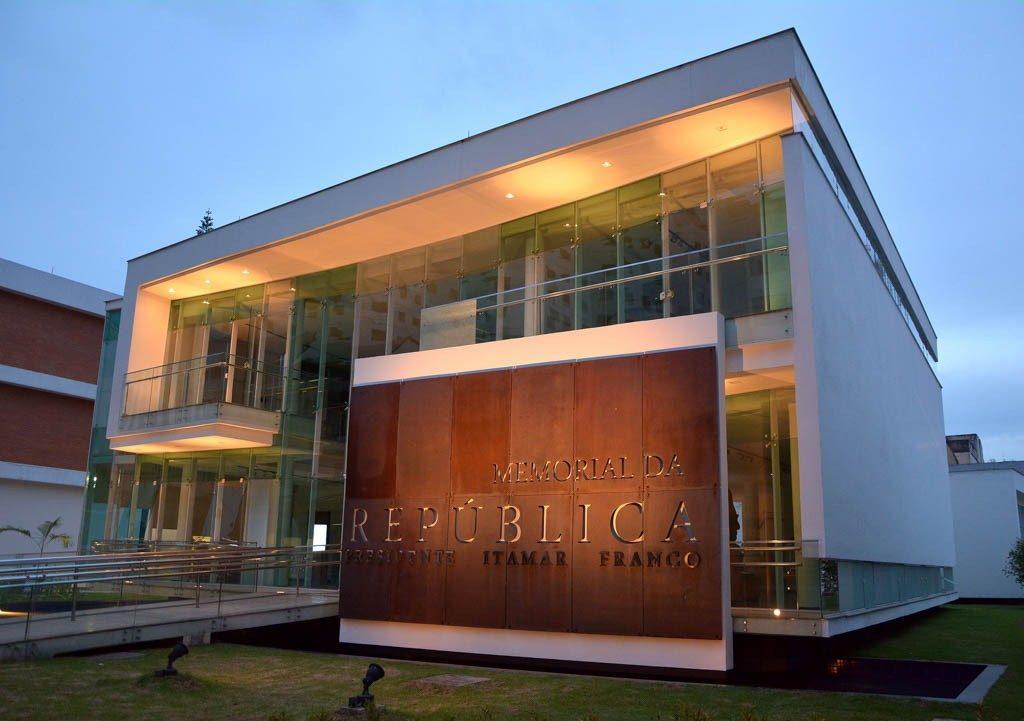 A foto mostra a fachada do Memorial da República Presidente Itamar Franco. À frente do Memorial, há uma placa informando o nome do prédio e, à esquerda, a rampa que dá acesso ao primeiro andar.