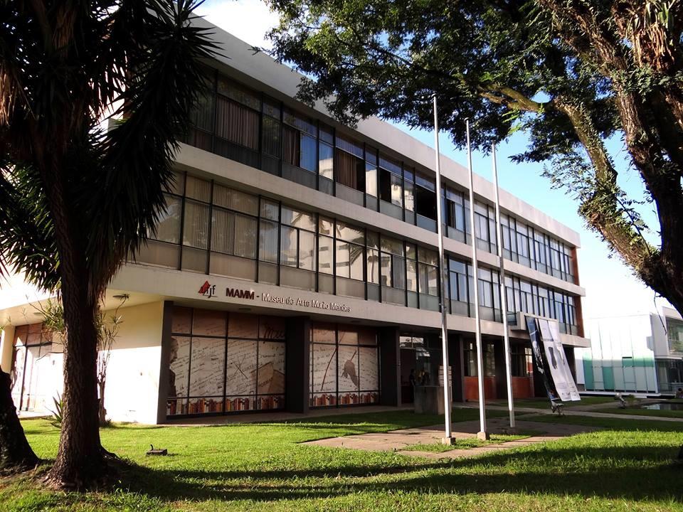 A imagem mostra a ampla fachada de vidro e linhas modernas do prédio do Museu de Arte Murilo Mendes. A área externa também apresenta um extenso gramado e algumas árvores.